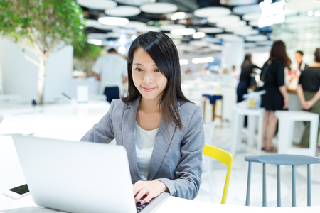 Businesswoman working on notebook computer at co work space Stock Photo
