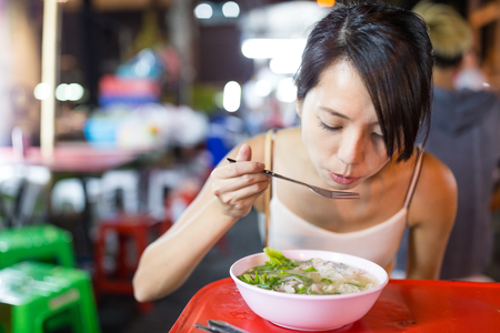 Woman eating in night market of bangkok city