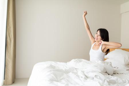 Vrouw die zich uitstrekt in haar bed