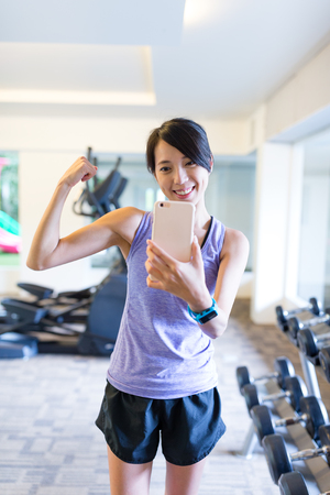 Young woman with smartphone taking mirror selfie in gym Stock Photo