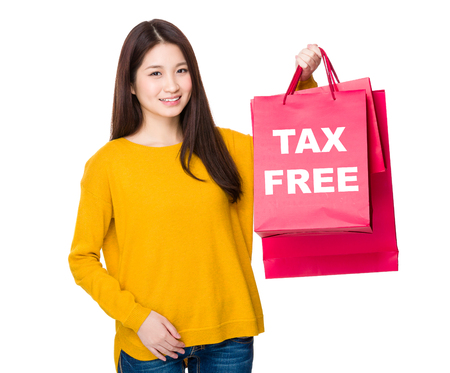 Woman hold with shoppong bag showing tax free