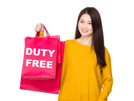 Woman hold with red shopping bag and showing duty free Stock Photo