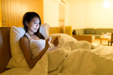 Femme asiatique utilisant un téléphone portable à la maison Banque d'images - 74660012