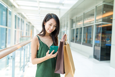 Woman holding shopping bag and using mobile phone