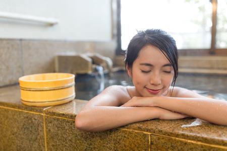 Aziatische vrouw geniet van onsen Stockfoto