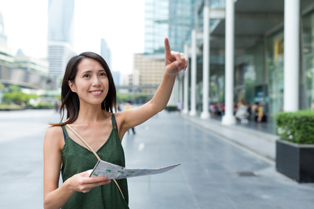 Woman holding city map and finger pointing far away in Bangkok city