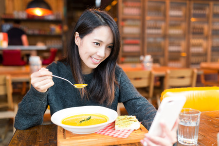 Woman having soup and taking selfie Stock Photo