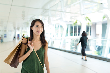 Woman holding shopping mall and walking in pedestrain foot path