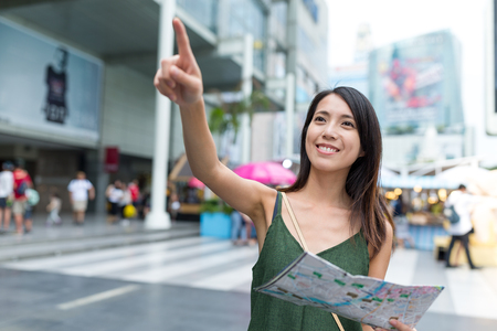 far away look: Woman using city map and finger pointing far away Stock Photo