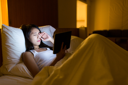 Woman feeling eye pain and looking on digital tablet at night