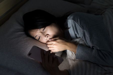Woman feeling tired and using mobile phone on bed