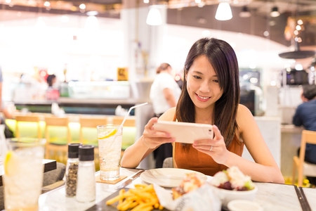 customer records: Woman taking photo in restaurant