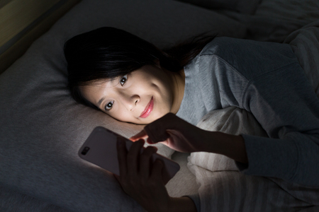 Woman watching on cellphone at night Standard-Bild