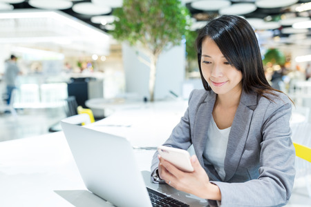 Businesswoman checking on cellphone and use of laptop computer