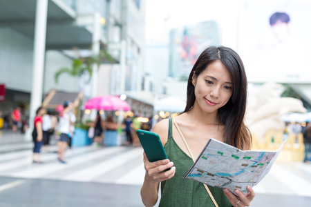 Woman using city map and cellphone in bangkok city