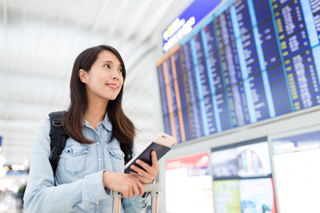 far away look: Woman checking on display screen at the airport