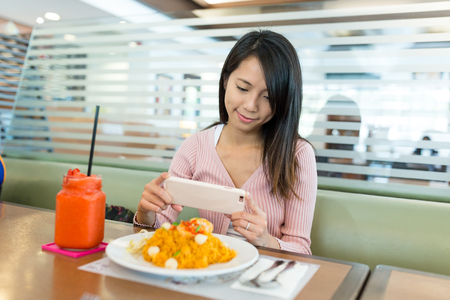 Woman taking photo in restaurant