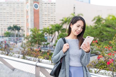 Femme travaillant sur téléphone portable à Hong Kong Banque d'images - 76603599