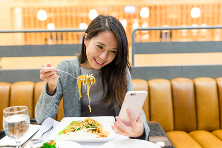 Woman use of mobile phone and eating together Banque d'images