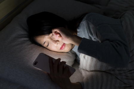 Woman feeling eye pain with using mobile phone on bed at night