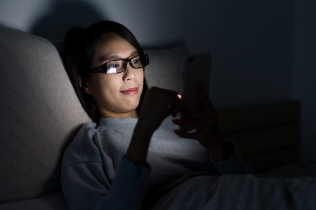 Woman working on cellphone at night