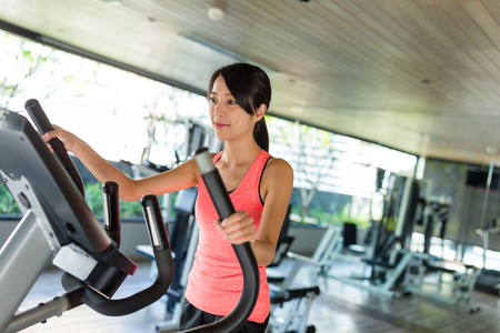 Sport Woman running on Elliptical machine