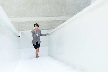 upstairs: Business woman talk to mobile phone and walking upstairs
