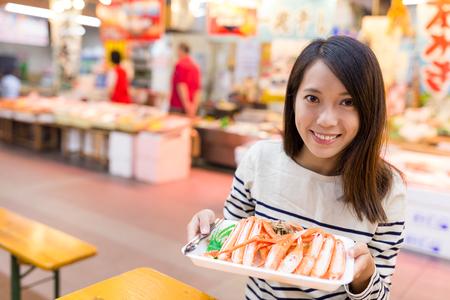 fish vendor: Woman holding tray of crab Stock Photo