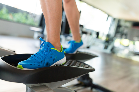 elliptic: Sport woman working out on elliptical trainer in gym
