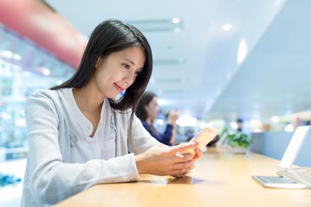 Vrouw die cellphone in koffiewinkel gebruikt