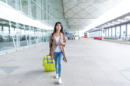 far away look: Woman go travel with her luggage and cellphone in airport