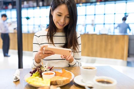 Woman taking photo on her dish Stock Photo