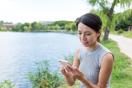 face in tree bark: Woman sending sms on cellphone in the park
