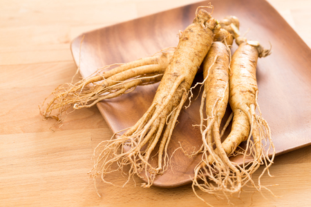 Ginseng root over wooden background