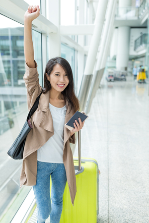 Happy woman go travel with cellphone and luggage Stock Photo