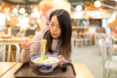 Young Woman eating ramen in restaurant