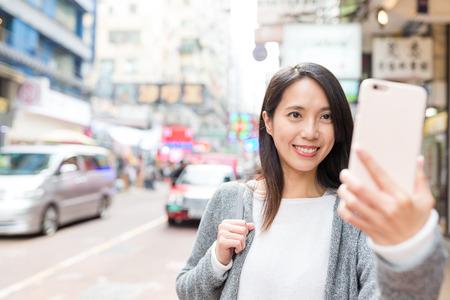 Vrouw die selfie door mobiele telefoon in Mongkok-stad nemen