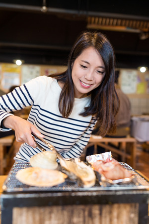 Young Woman enjoy seafood barbecue