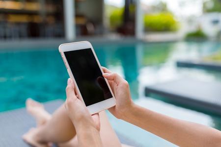 Jonge vrouw met behulp van mobiele telefoon in het zwembad Stockfoto