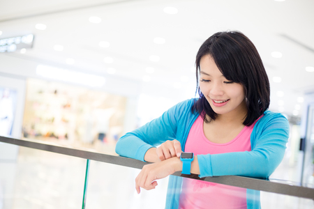 Woman using smart watch in shopping mall