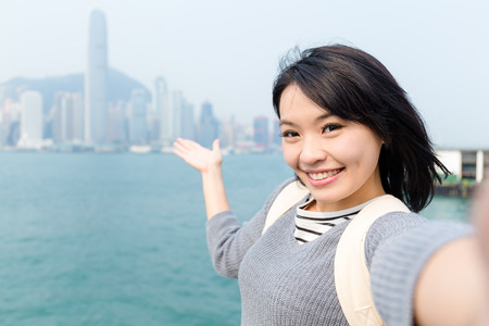Woman take selfie and showing the skyline of Hong Kong