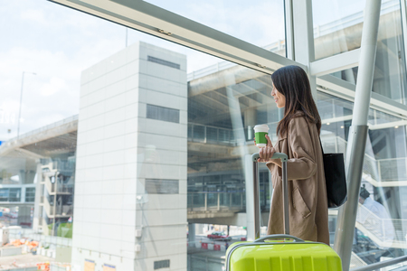 go inside: Woman holding a cup of coffee in airport