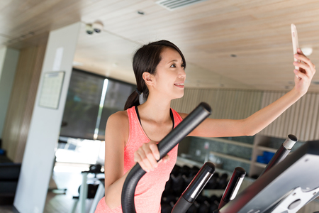 Woman training on Elliptical machine and taking selfie in gym