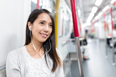 Woman listen to music on train Stock Photo