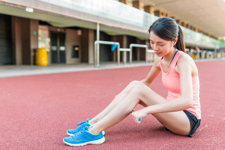 Woman using stick massage roller on legs