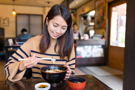 sit down: Woman eating japanese udon