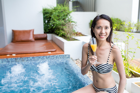 Woman enjoy jacuzzi spa and drink Stock Photo