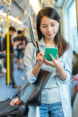 hands free phone: Woman listen to song on phone and taking the train Stock Photo