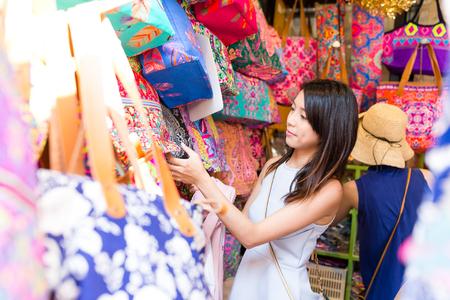 Aziatische vrouw die in weekendmarkt winkelt