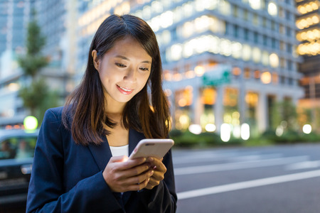 Business woman use cellphone in Tokyo city